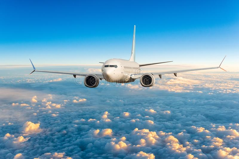 Front view of aircraft in flight. The passenger plane flies high above the clouds and blue sky. Business travel and. Summer trip concept royalty free stock image