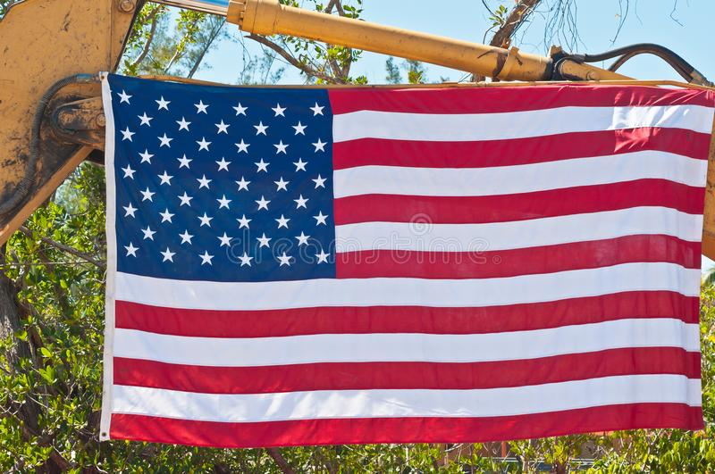 Front view of American flag at a construction sight. Front view, close up of American flag hanging from heavy equipment at a tropical construction sight on a stock photography