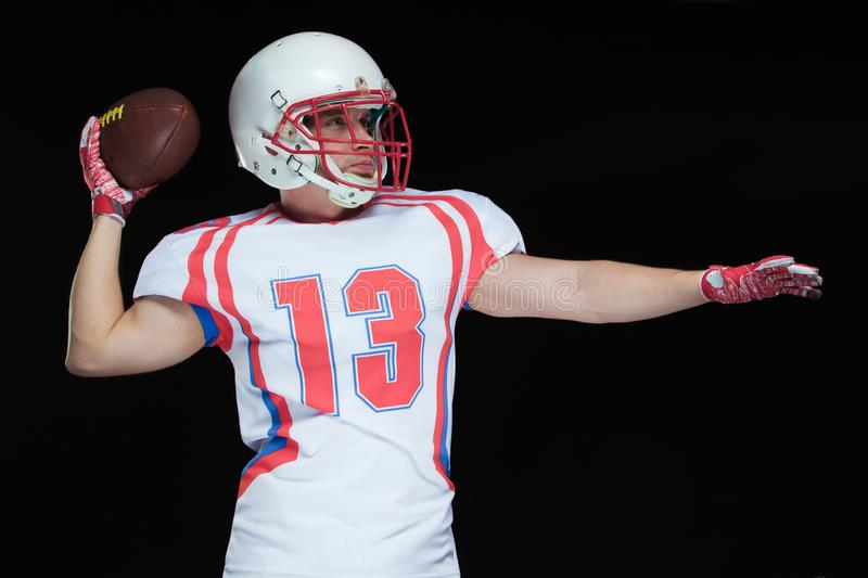 Front view of American football player wearing helmet throwing ball standing against black background stock photos