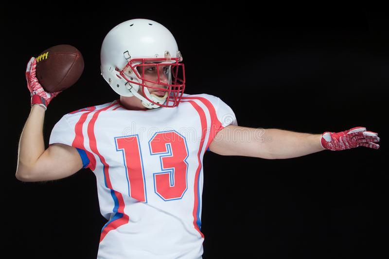 Front view of American football player wearing helmet throwing ball standing against black background stock photo
