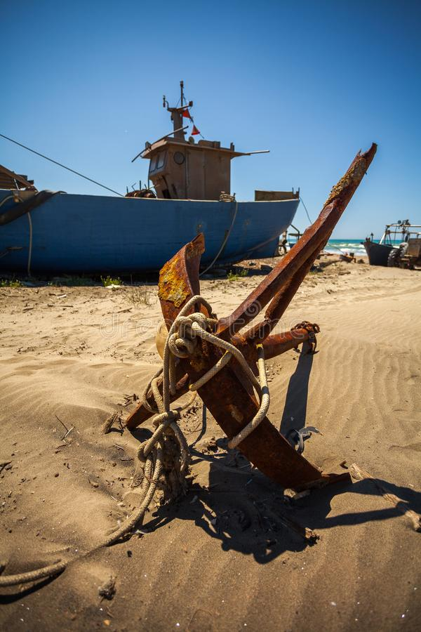 A front view of an anchor in front of a big fishing boat on the beach.  stock images