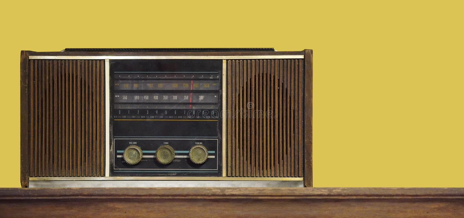 Front view antique brown radio on wooden background,wall yellow background,technology background,copy space stock photography