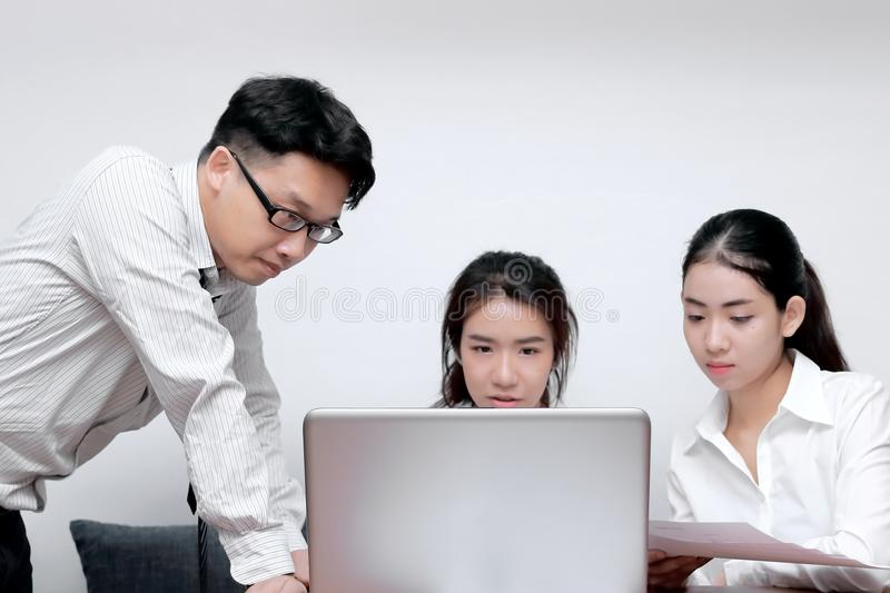 Front view of Asian business people with laptop working together in modern office. Selective focus and shallow depth of field. royalty free stock image