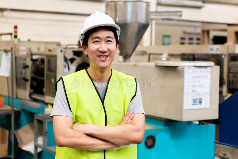 Smiling factory worker with safety hard in industrial facilities stock images