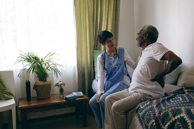 Female doctor and senior male patient interacting with each other stock photo