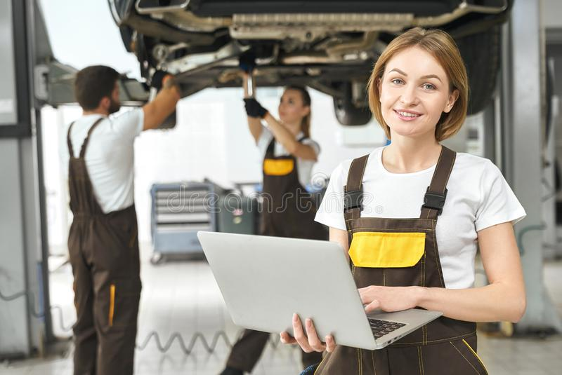 Front view of attractive woman working at auto service stock images