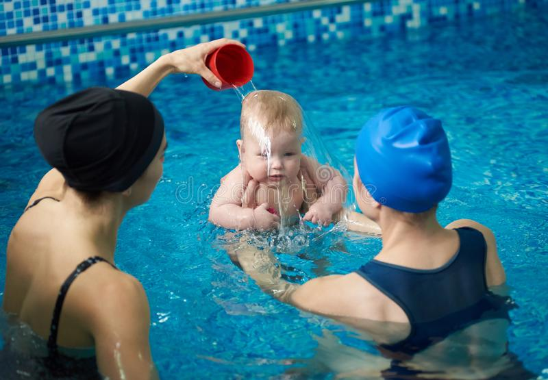 Front view of baby boy during swimming lesson. Back view of mother holding child and woman pouring water on child`s head royalty free stock images