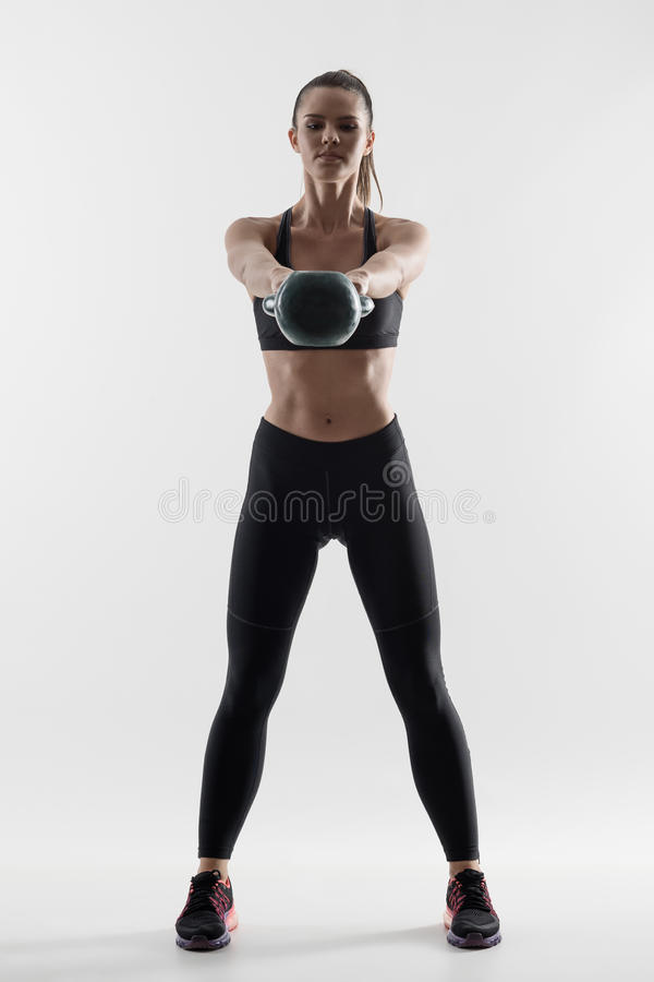 Front view back lit silhouette of strong fit woman doing kettlebell swing training exercise. royalty free stock photography