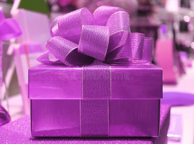 Front View of a Beautiful Shiny Purple Square Gift Box with Glitter Purple Ribbon Bow stock photos
