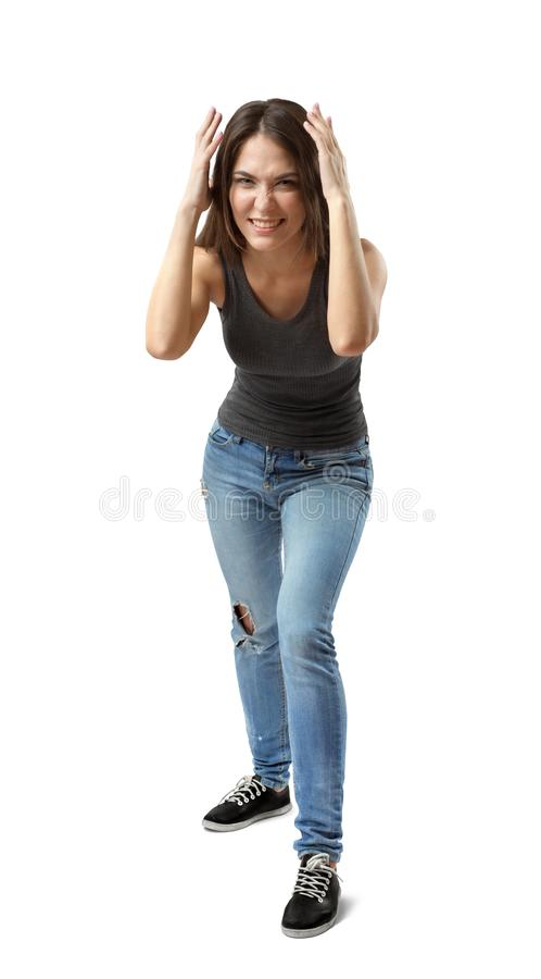 Front view of beautiful woman in gray top and blue jeans standing and leaning forward, with hands on head, smiling and royalty free stock photos