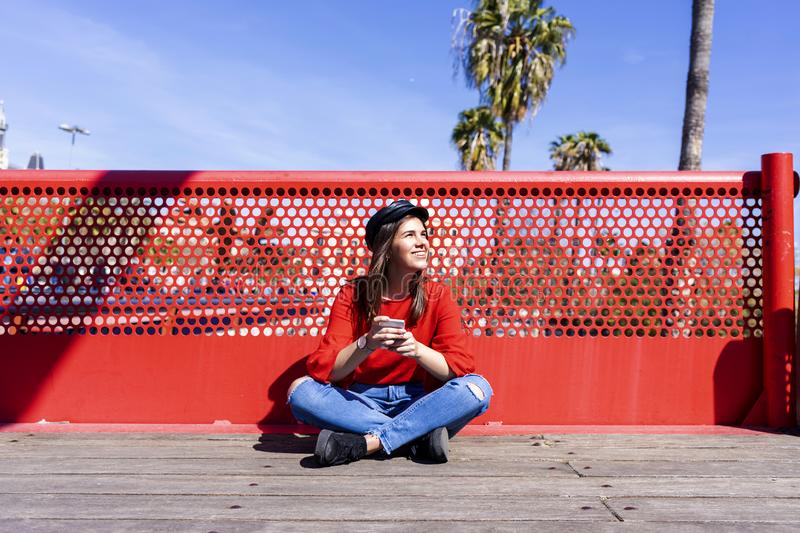 Front view of a beautiful young woman wearing urban clothes sitting on a bridge floor while using a mobile phone outdoors in a royalty free stock photography