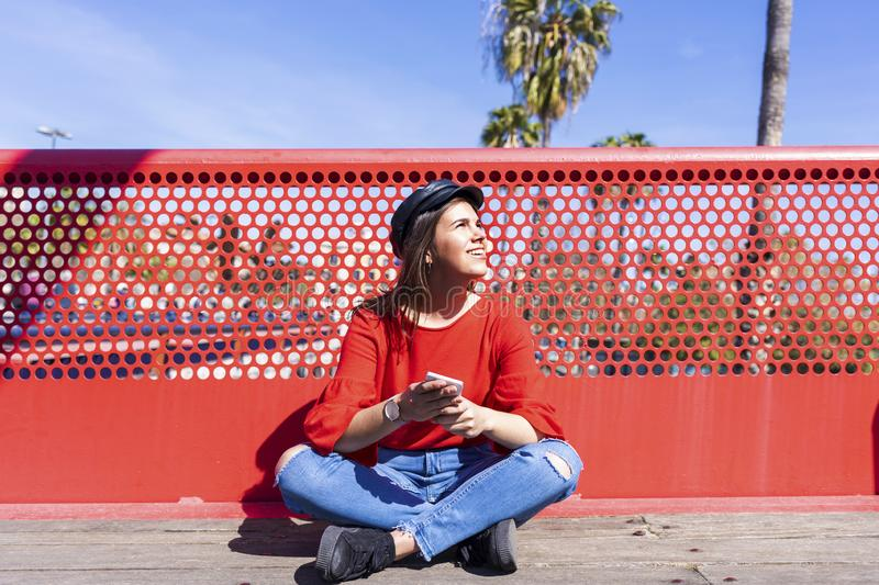 Front view of a beautiful young woman wearing urban clothes sitting on a bridge floor while using a mobile phone outdoors in a stock images
