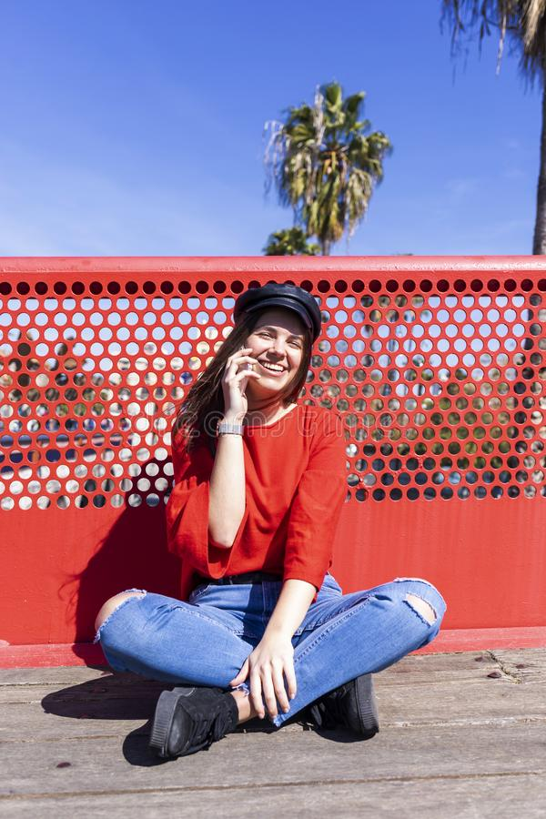 Front view of a beautiful young woman wearing urban clothes sitting on a ground while using a mobile phone outdoors in the street stock photos
