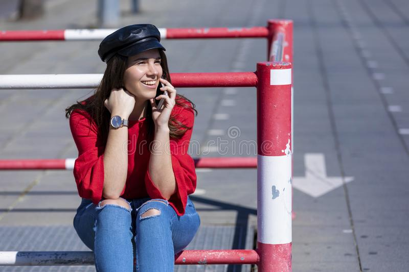Front view of a beautiful young woman wearing urban clothes sitting on a metallic fence while using a mobile phone outdoors in the royalty free stock photos