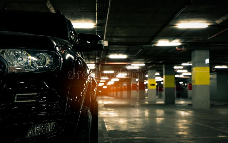 Front view of black car parked at underground car parking of shopping mall. Parking lot of shopping mall in the evening. royalty free stock photography