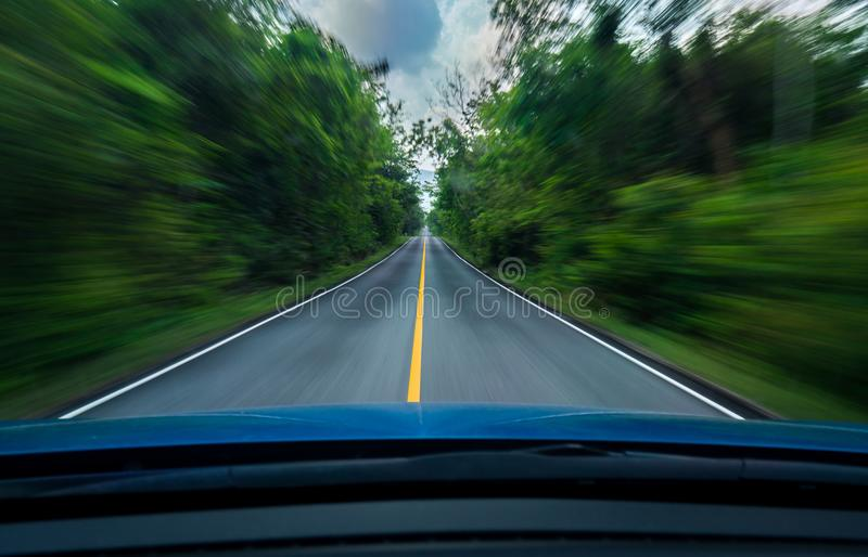 Front view of blue car driving with fast speed on the middle of asphalt road with white and yellow line of traffic symbol. In the green forest. Trees beside the royalty free stock images