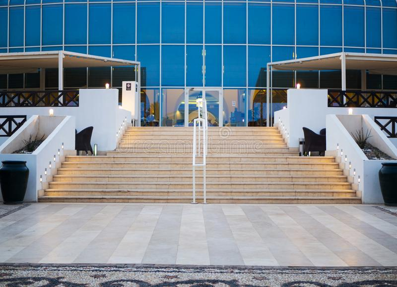 Front view of blue glass building entrance with stairs. Modern glass building entrance with stairs, nobody stock image