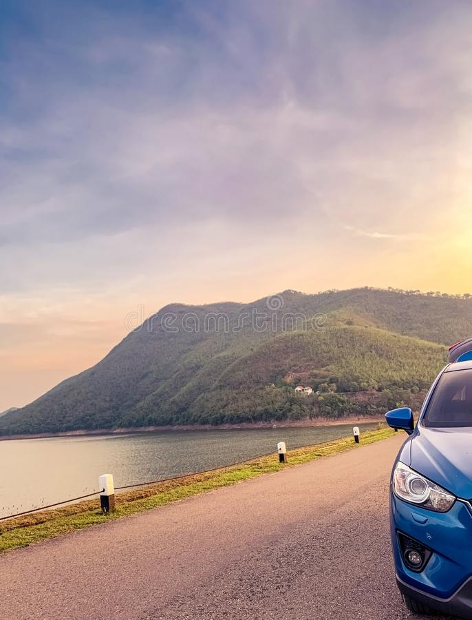 Front view of blue SUV car with opened car truck parked on asphalt road at dam. Summer road trip travel. Car parked on the road. In front of the mountain beside stock images