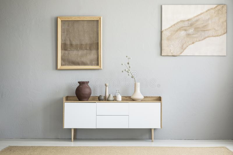 Front view of burlap artworks on a light gray wall stock image