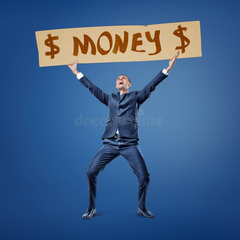 Front view of a businessman holding up the title `Money` with dollar signs on both sides. royalty free stock photos