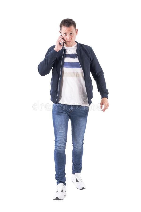 Front view of busy serious casual man talking on the phone walking with intense stare at camera. Full body isolated on white background royalty free stock images