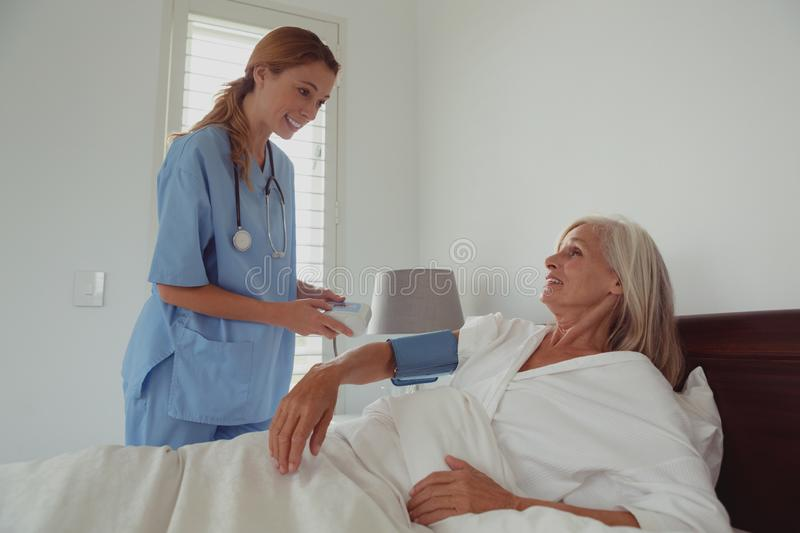 Female doctor checking blood pressure of active senior woman in bed in bedroom stock photo
