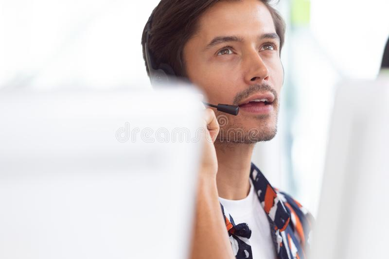 Male customer service executive working on computer at desk. Front view of Caucasian male customer service executive working on computer at desk in office stock photo