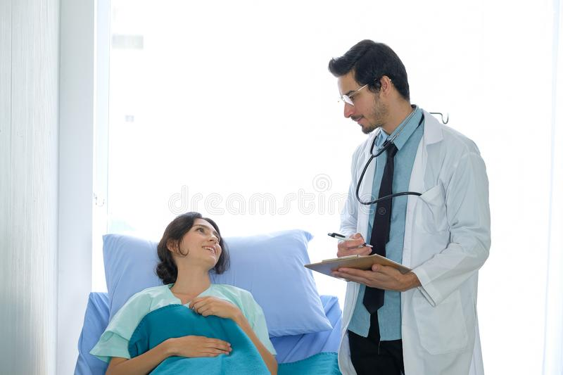Front view of Caucasian male doctors and female patients, talking about illness and taking notes in the ward at hospital royalty free stock images