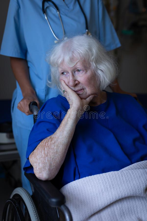 Surgeon pushing the wheelchair of a sad senior female patient stock image