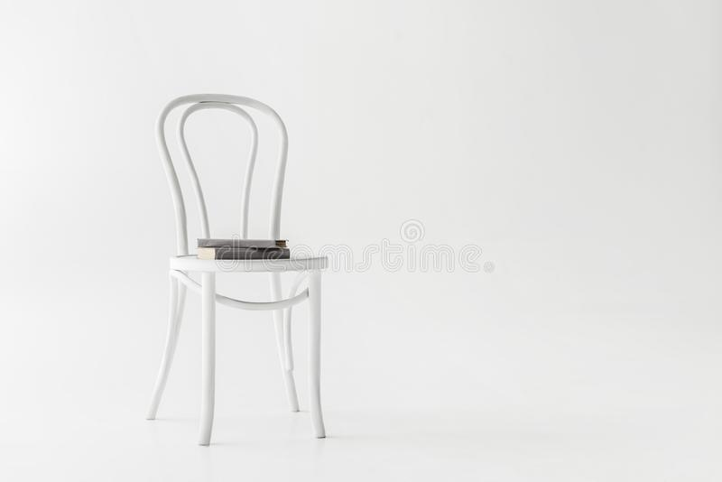 Front view of chair with two books. Isolated on grey background royalty free stock image