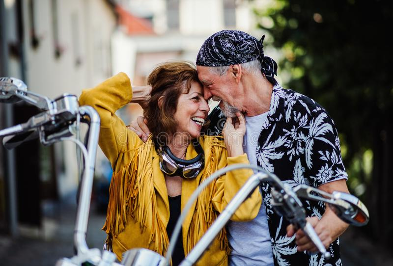 A cheerful senior couple travellers in love with motorbike in town. A front view of cheerful senior couple travellers in love with motorbike in town royalty free stock image