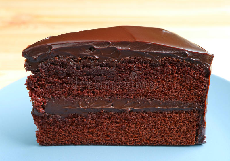 Front view of Chocolate Layer Cake Served on Wooden Table. Blurred Background royalty free stock photo