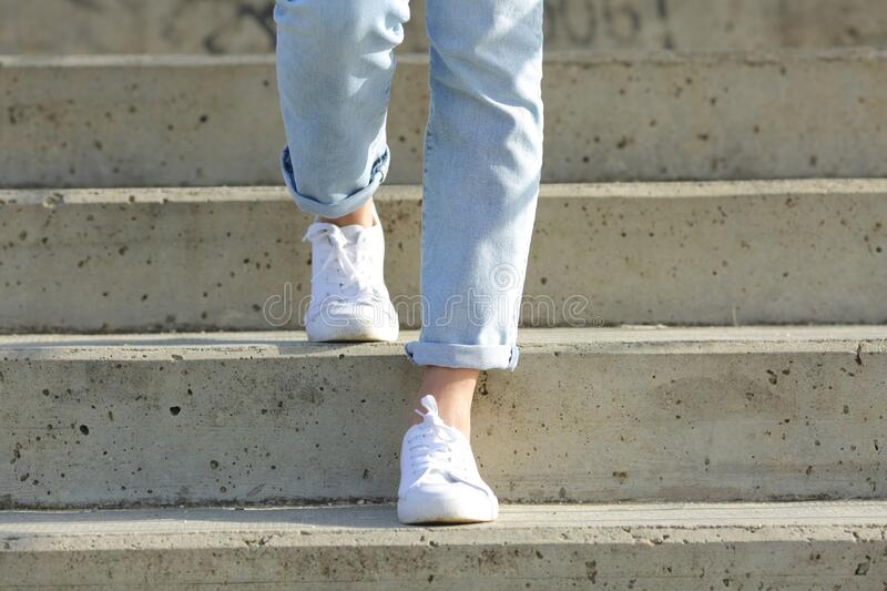 Woman legs wearing sneakers walking down stairs royalty free stock photo