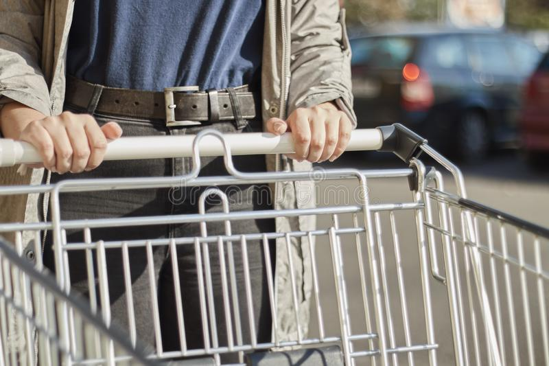 Front view closeup with a selective focus of a teenage girl moving a shopping cart outside a supermarket royalty free stock images
