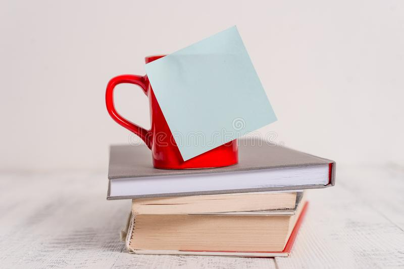 Front view coffee cup mug hot drinks blank colored sticky note stacked piled books lying retro vintage rustic old table royalty free stock photos