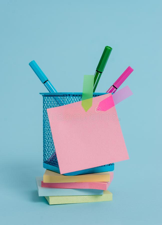 Front view colored sticky note arrow banners stacked metal pens holder lying beautiful pastel background. Blank text stock photo