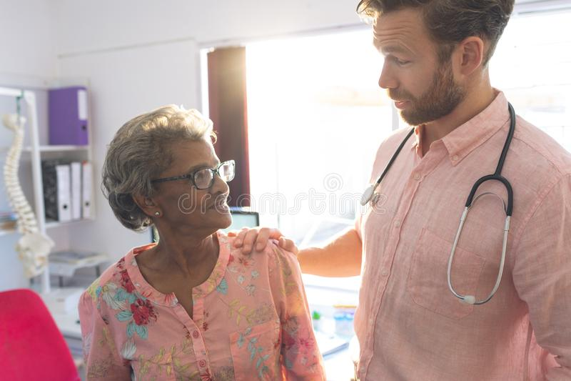 Confident male doctor interacting with female senior patient in clinic royalty free stock photos