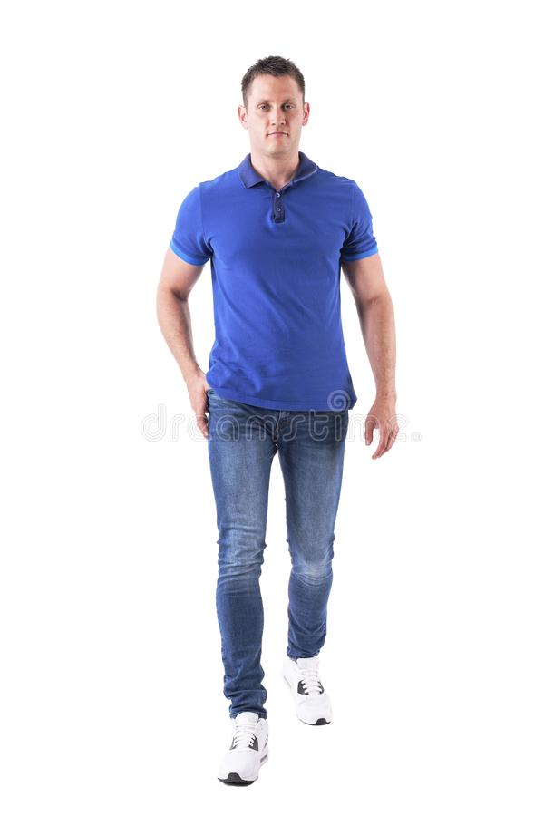 Front view of confident young adult man walking forwards and looking at camera in blue polo shirt. Full body isolated on white background royalty free stock photos