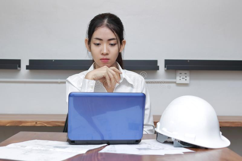 Front view of confident young Asian businesswoman working on the workplace in modern office. Thinking and thoughtful business conc royalty free stock photo