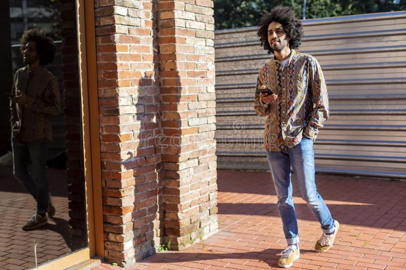 Front view of a cool young smiling afro man using a mobile phone while standing outdoors in a sunny day royalty free stock image