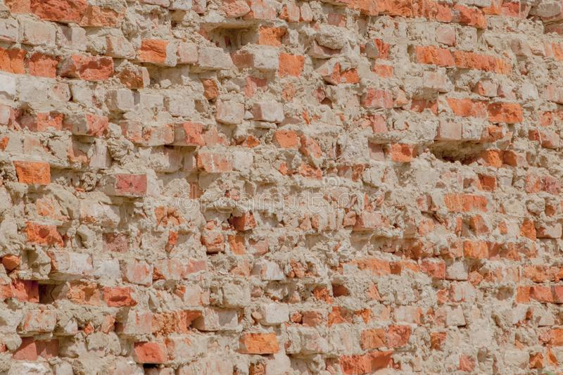 Front view of the cracked red clay brick wall of a residential building stock image