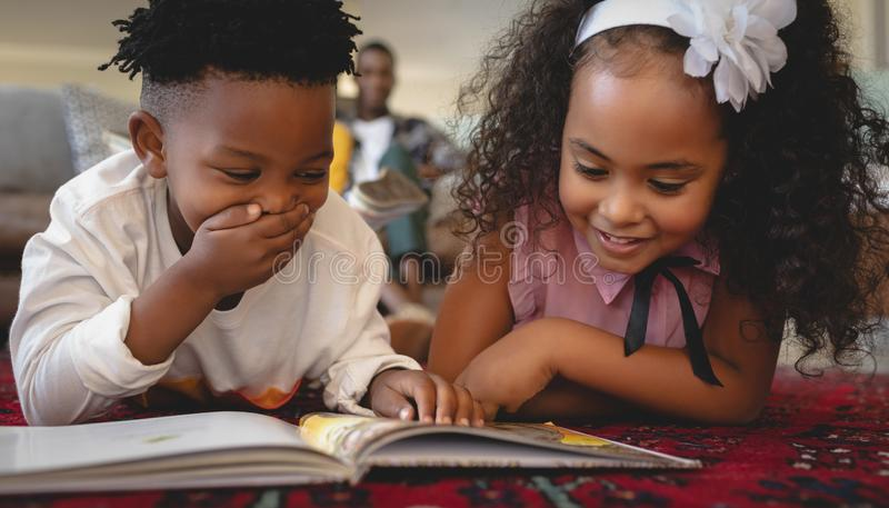 Cute African American sibling lying on floor and reading a storybook royalty free stock image