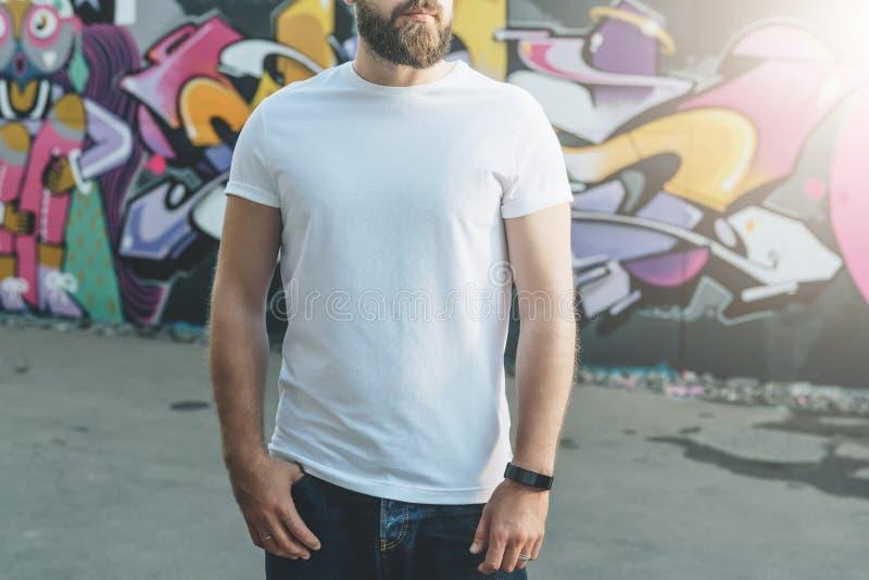 Front View De jonge gebaarde hipstermens gekleed in witte t-shirt is tribunes tegen muur met graffiti Spot omhoog royalty-vrije stock afbeelding