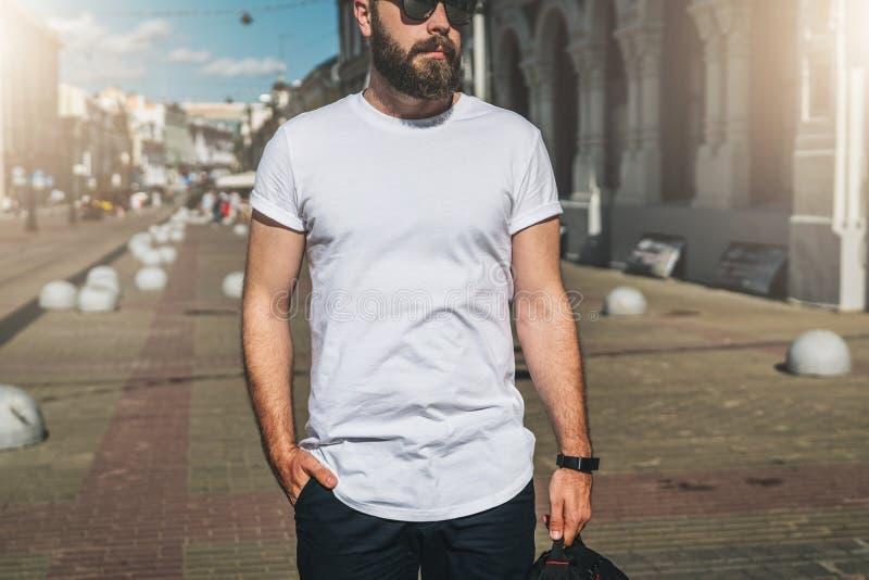 Front View De jonge gebaarde millennial mens gekleed in witte t-shirt en zonnebril is tribunes op stadsstraat Spot omhoog royalty-vrije stock foto's
