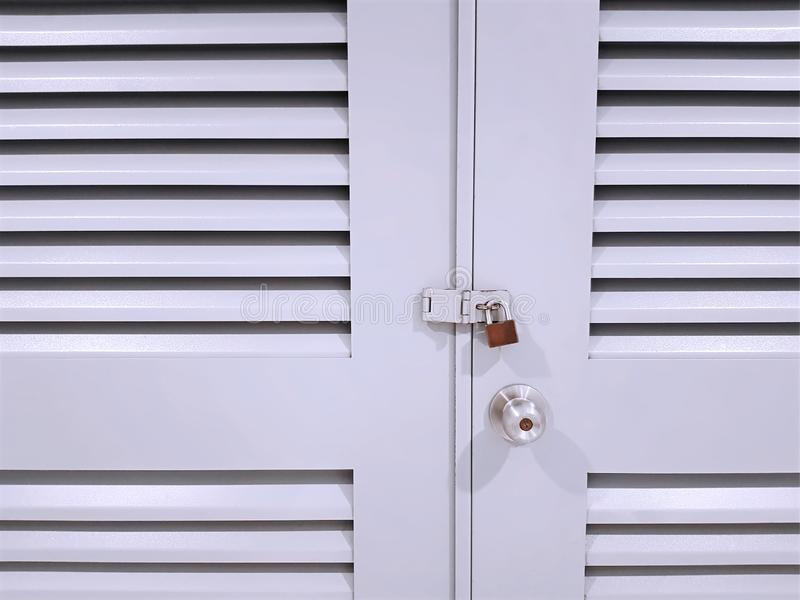Front View de la porte verrouill?e en bois blanche avec des grils de ventilation photographie stock