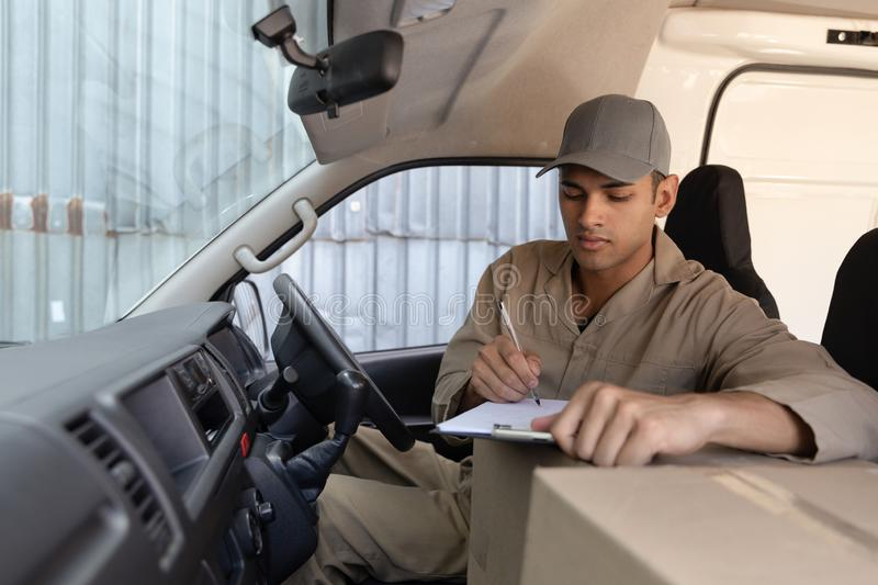 Delivery man with cardboard boxes writing on clipboard in front seat of car outside the warehouse. Front view of delivery man with cardboard boxes writing on royalty free stock image
