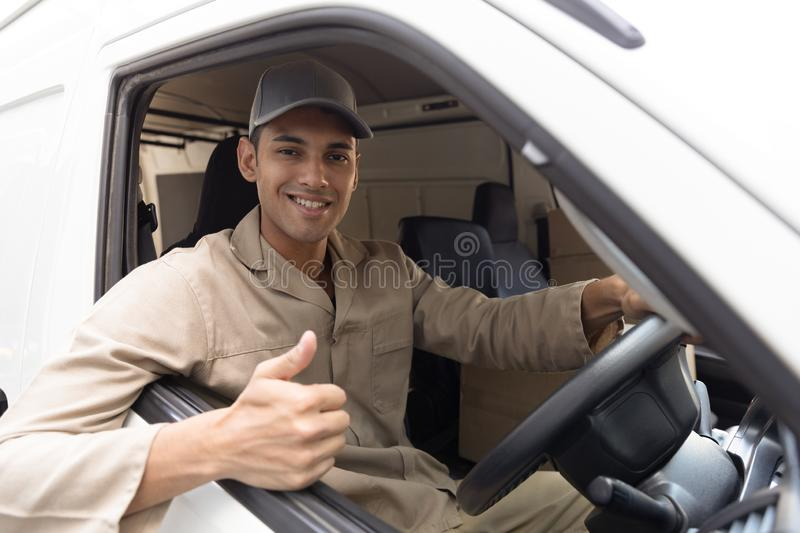 Delivery man showing thumbs up while sitting in front seat of car outside the warehouse. Front view of delivery man showing thumbs up while sitting in front seat stock photography
