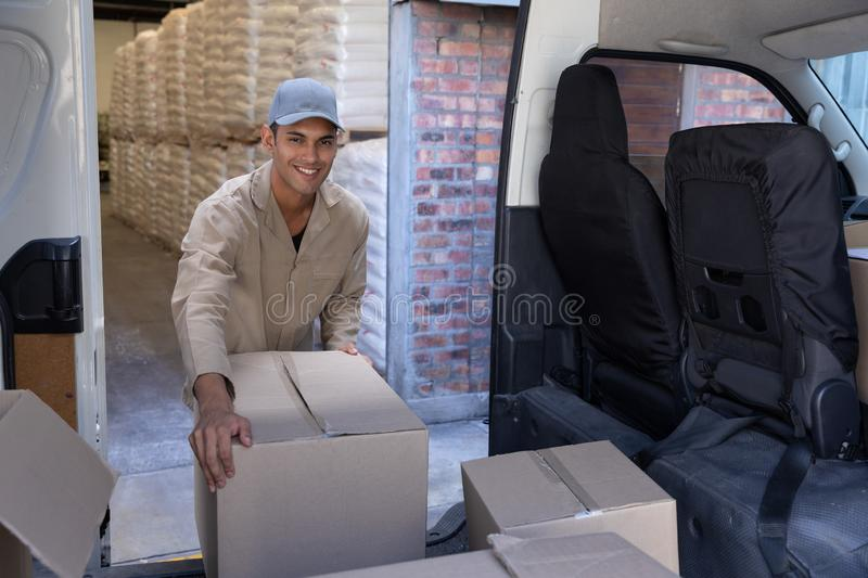 Delivery man unloading cardboard boxes from a van outside the warehouse. Front view of delivery man unloading cardboard boxes from a van outside the warehouse stock images