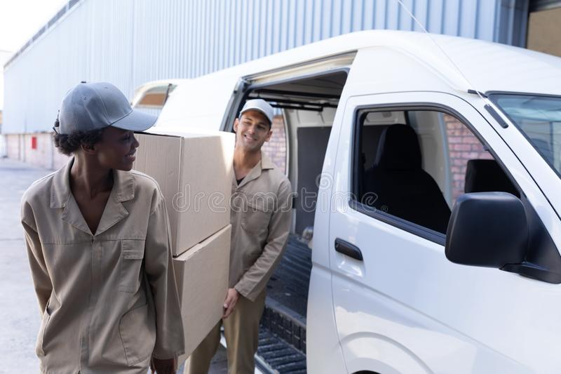 Delivery man and woman carrying cardboard boxes near van outside the warehouse. Front view of delivery man and woman carrying cardboard boxes near van outside stock photo