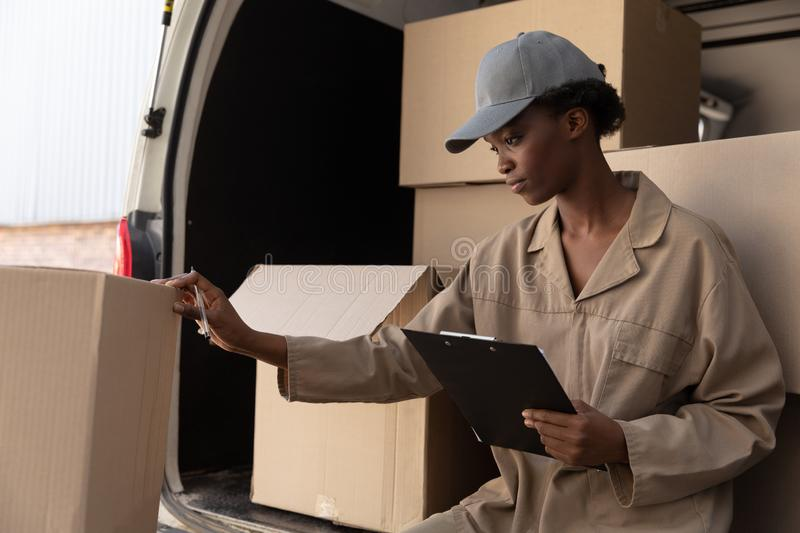 Delivery woman checking parcel near van outside the warehouse stock image